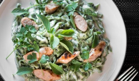 An overhead photo of green sausage pasta.