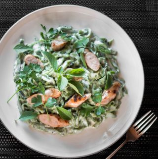 Cheesy fresh green pasta served with grilled sausages on a plate with a fork on the side.