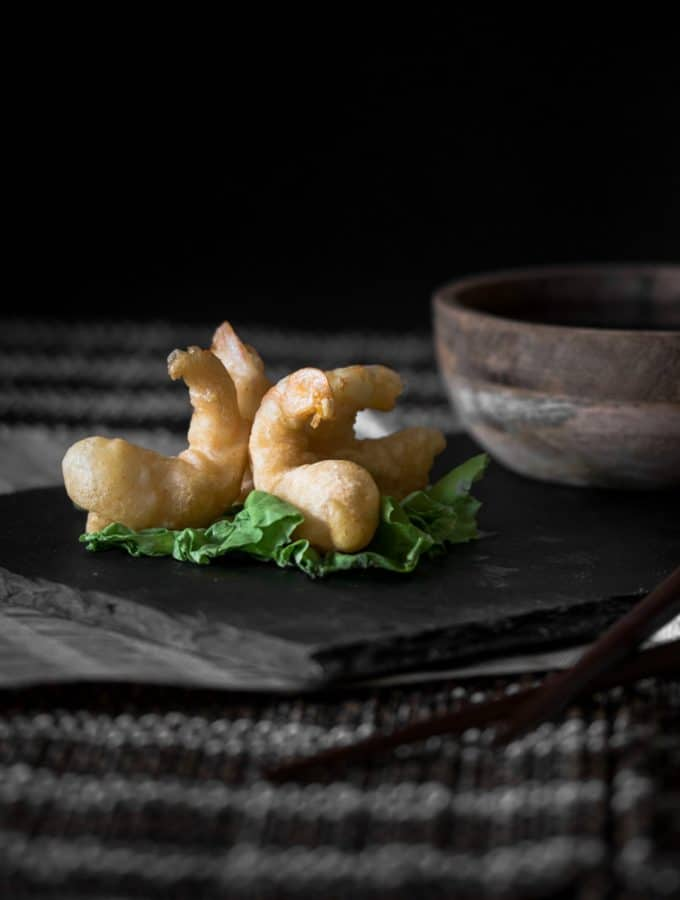 A dark contrast photo of tempura prawns served on a sushi platter, garnished with a bundle of lettuce.