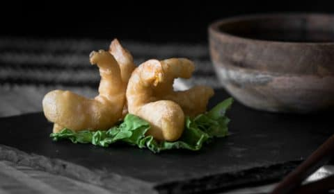 Tempura prawns served on a sushi platter and garnished with a bundle of lettuce.
