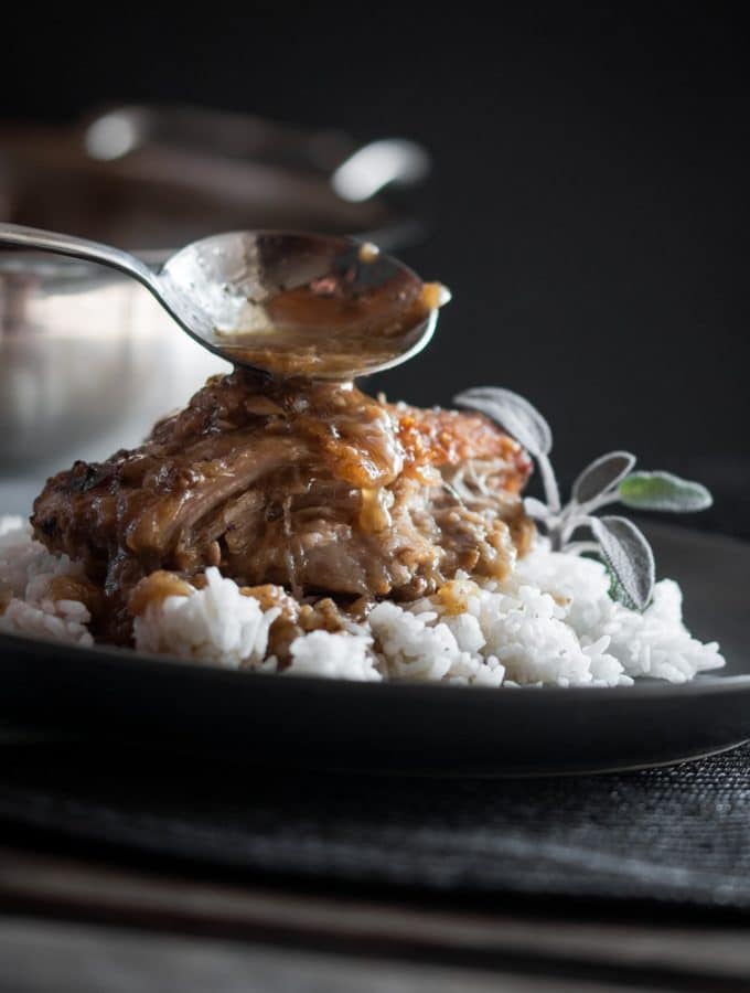 Pork cheeks served on rice and garnished with sage.