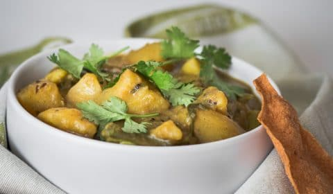 A photo of potato and green bean curry serve in a white bowl.