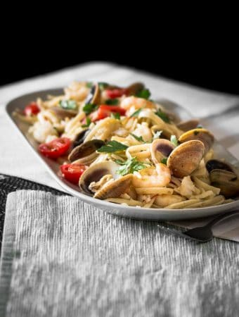 A moody contrast photo of pasta filled with clams, prawns and fish.