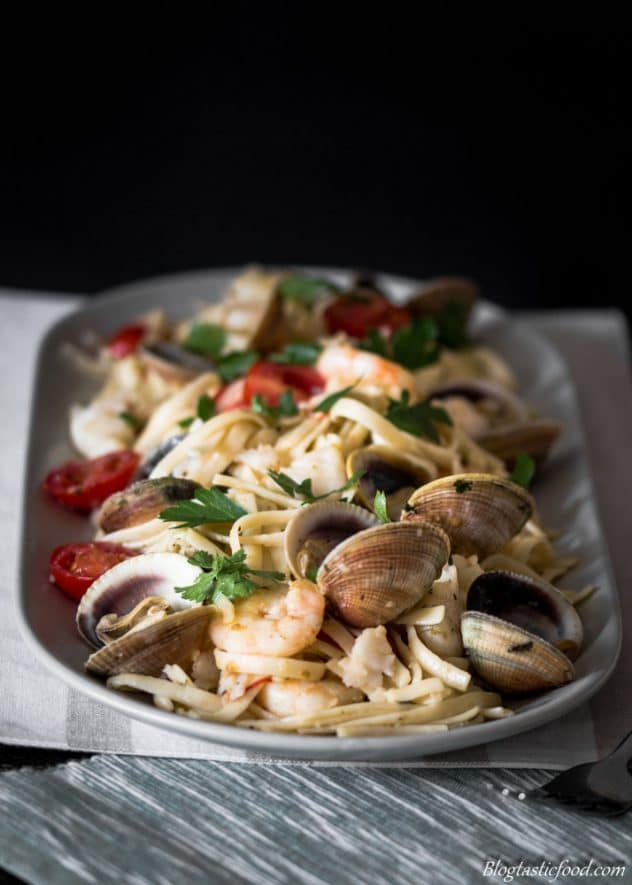 A photo of seafood linguine pasta served on a grey plate.