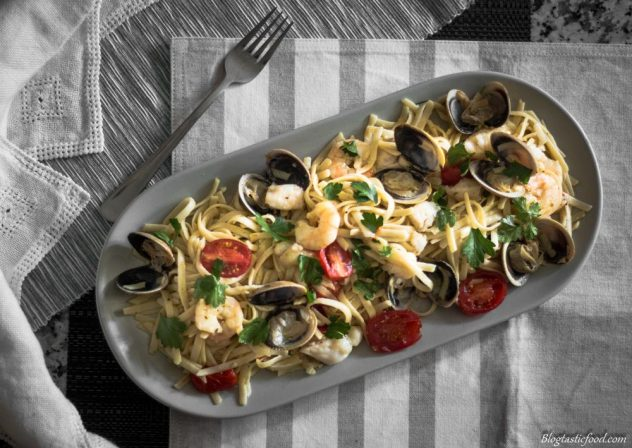 An over head photo of seafood pasta served on a grey long plate.