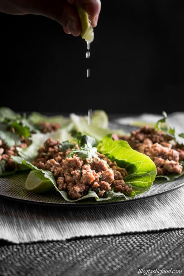 lime juice being squeezed over minced meat in lettuce wraps.