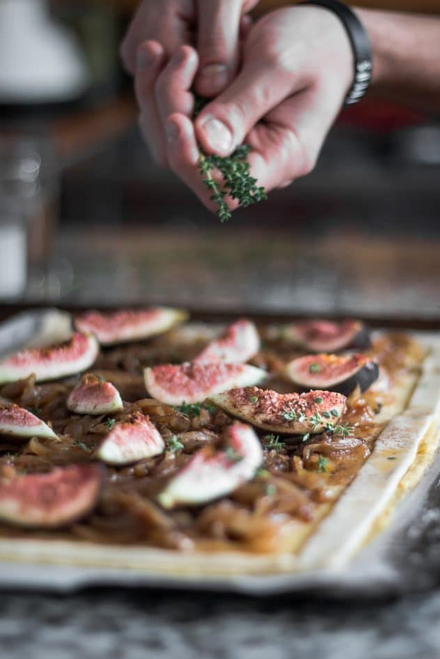 Fresh thyme being sprinkled over a raw fig and onion tart.