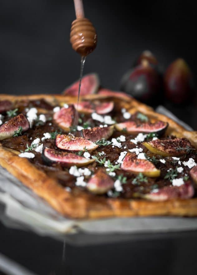 A photo of a fig and onion tart with honey being drizzled over the top.