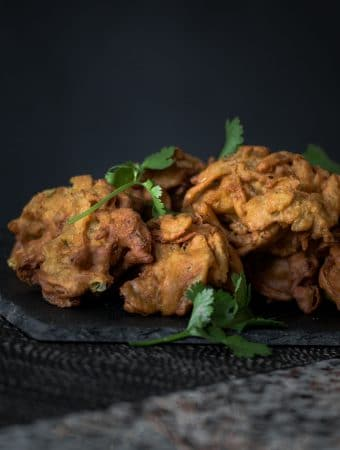 A photo of golden onion bhajis and coriander served on a platter.