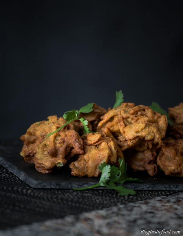 An eye level photo of onion bhajis that have been garnished with coriander.