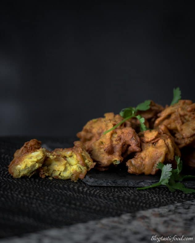 a photo of one among a group of onion bhajis that has been cut in half.