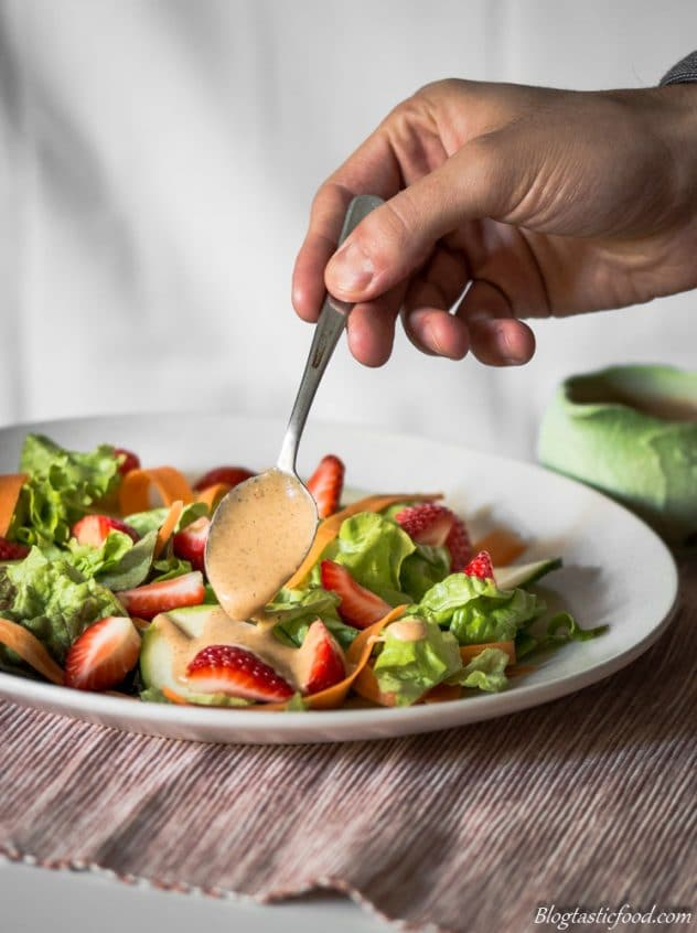 A photo of strawberry vinaigrette being spooned of a simple fresh salad of lettuce, slivered carrot and strawberries. Served on a nice white plate.