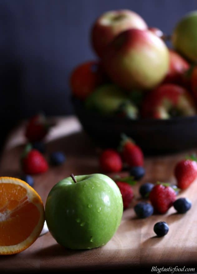 An eye level photo of apples, half an orange, strawberries and blueberries on a board. There's also a bowl of apples in the background.