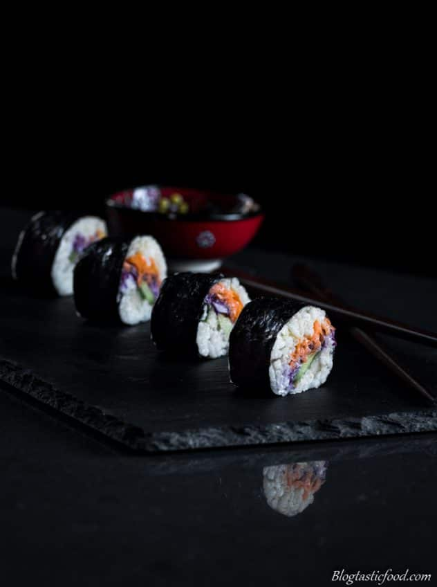Vegetable filled sushi served neatly on a slate with a dipping sauce bowl filled with soy sauce in the back ground.