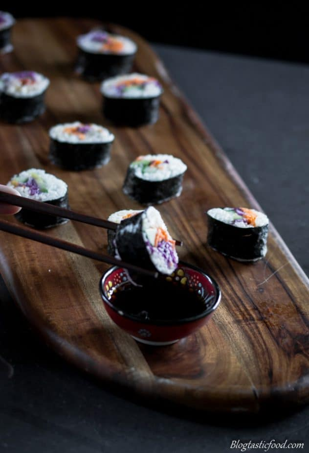 Veggie filled sushi served on a board with one of the sushi being picked up with chopsticks, and being dunked in soy sauce.