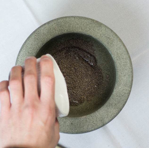 A photo of water being added to crushed chai seeds.