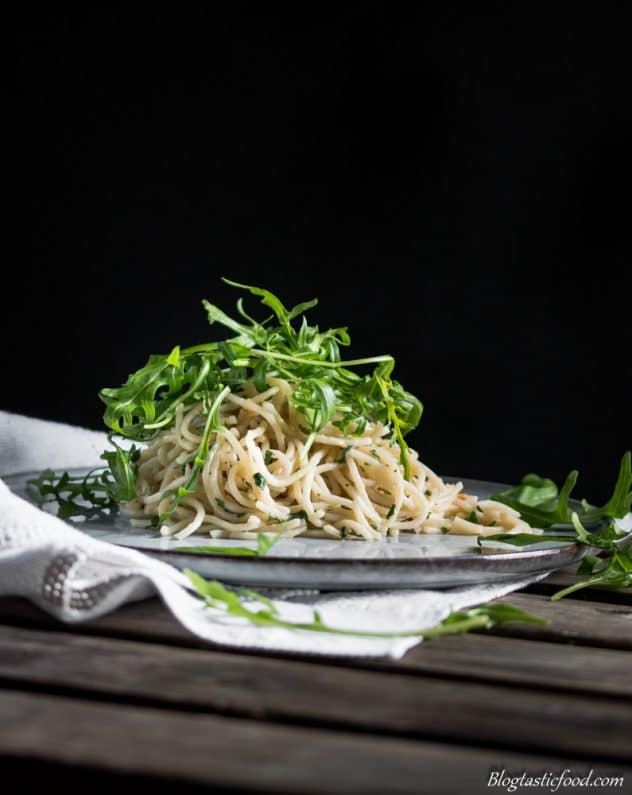 An eye level photo of aglio e olio pasta with rocket leaves on top. Served on a nice, flat plat on a white piece of a cloth.