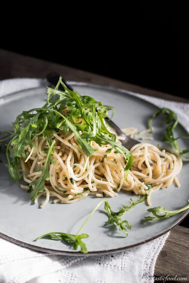 A 90 degree angle photo of aglio e olio pasta with rocket leaves on top and a fork twirling up some of the pasta. Served on a nice, flat plat on a white piece of a cloth.