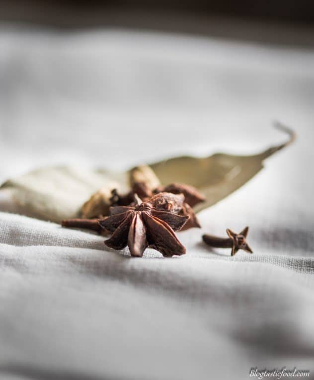 A couple of star anise, some cloves, some cardamom pods and a bay leaf on some white cloth.
