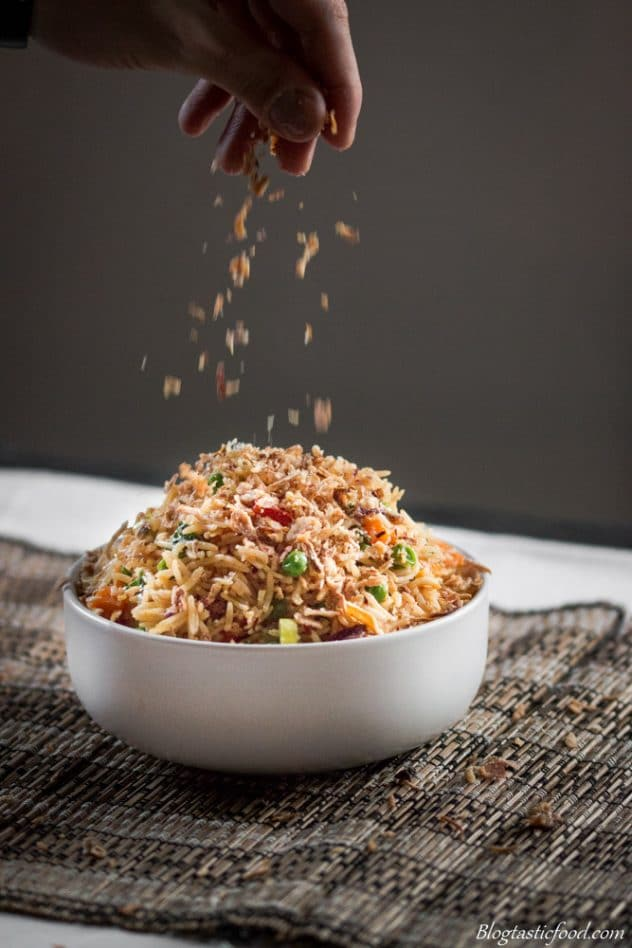 Some crispy fried shallots being sprinkled over a big bowl of fried rice,