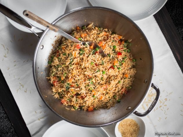 An overhead photo of fried rice in a wok surround by plates ready to be served.