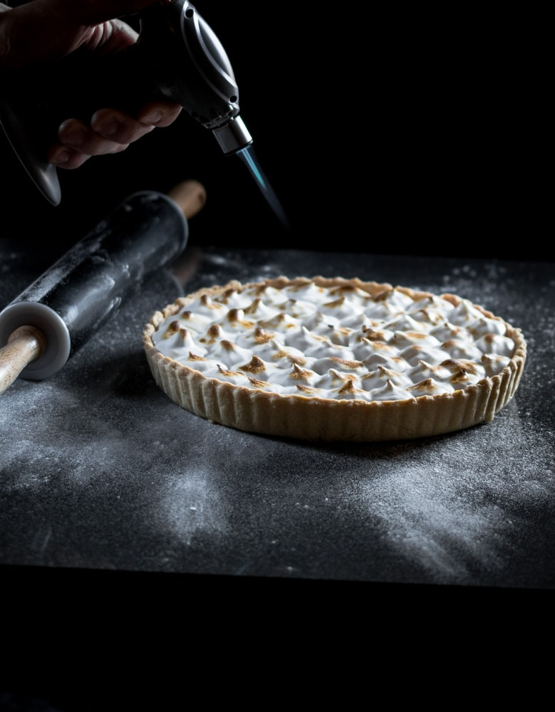 A vegan lemon meringue pie being caramelised with a blow torch.