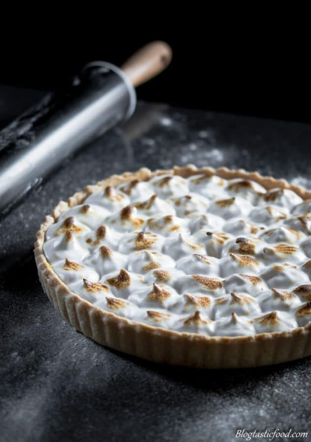 A photo of a vegan lemon meringue pie with flour dusted round it.
