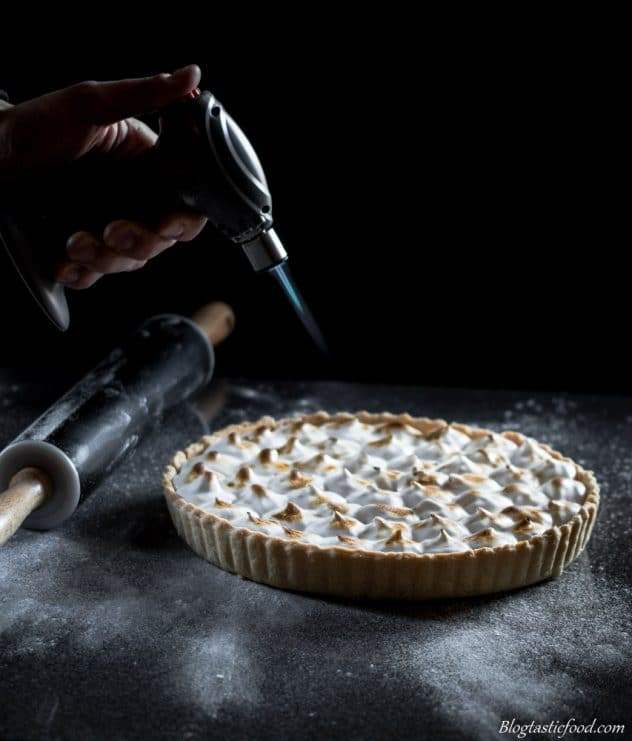A dark contrast photo of vegan lemon meringue pie being caramelised with a blow torch.