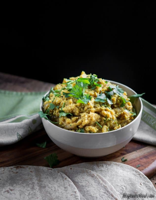 A contrast photo of red lentil dhal garnished with fresh coriander.