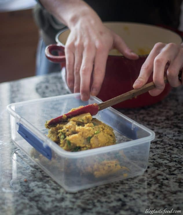 Red lentil dhal being transferred to a plastic container.