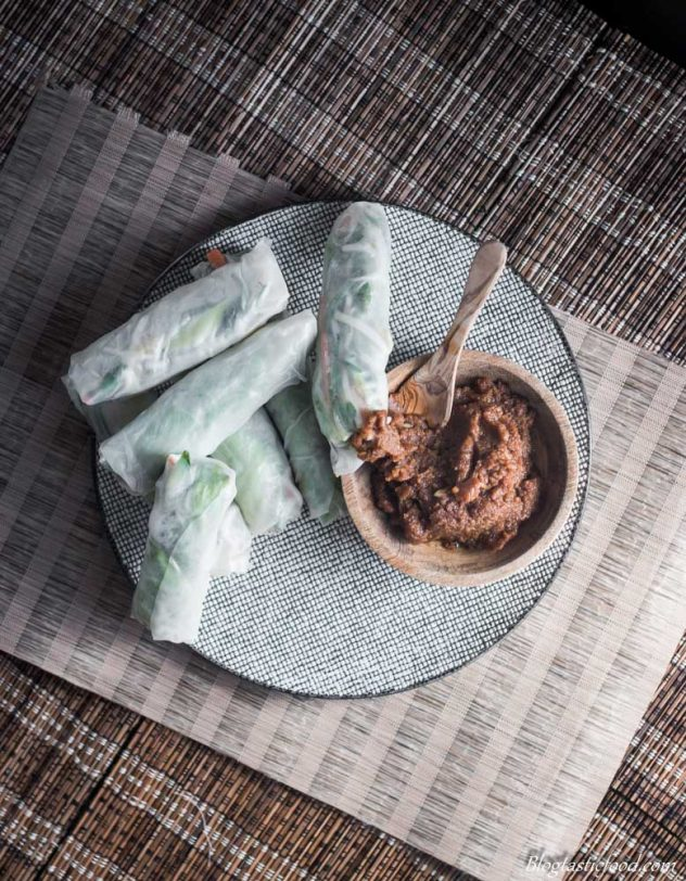An over-head photo of fresh Vietnamese rice paper vegetable filled spring rolls with a small wooden bowl filled with spicy peanut satay sauce.