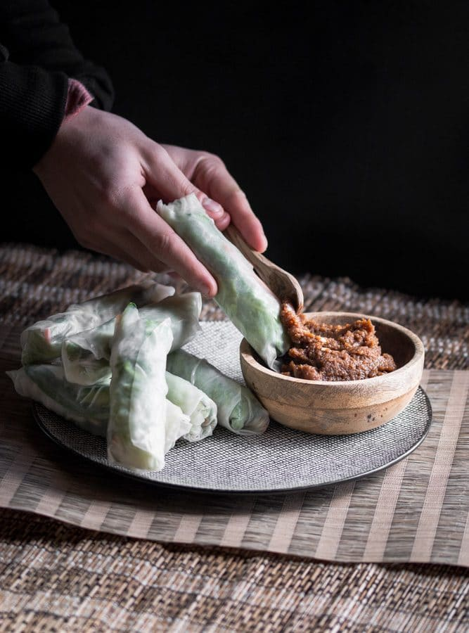 A dark, moody photo of fresh Vietnamese spring rolls on a plate and a small wooden bowl filled with peanut satay sauce. In the photo someone is also spooning some peanut satay sauce on one of the spring rolls.