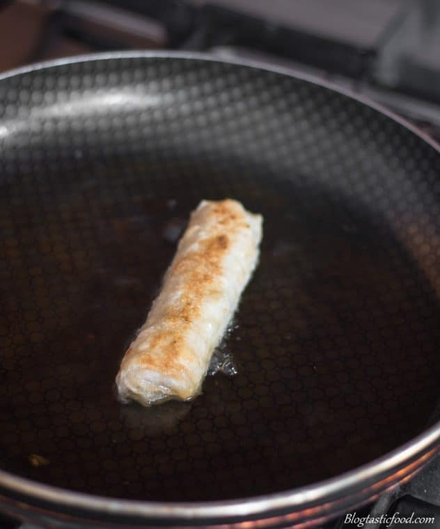 A Vietnamese srping roll being shallow fried in a non-stick pan.