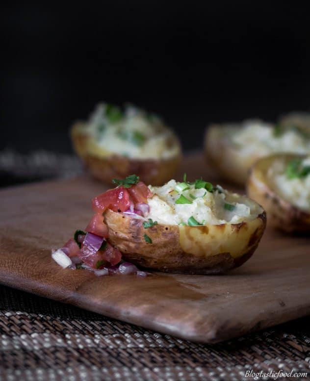 Twice baked potatoes on a board served with fresh salsa.
