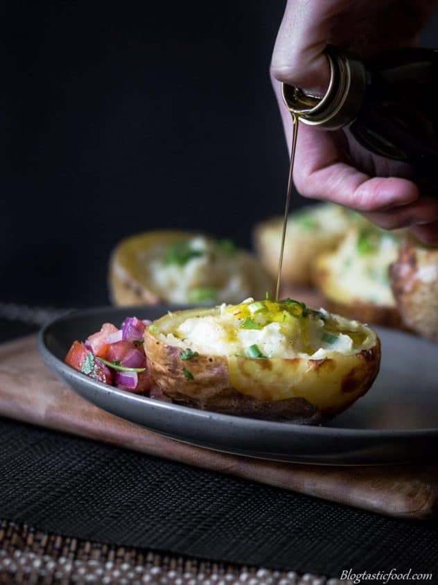 Extra virgin olive oil being drizzled over twice baked potatoes served with fresh salsa.