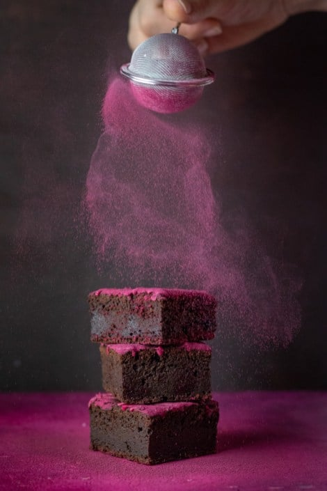 A eye level photo of chocolate beetroot brownies getting dusted with icing sugar and beetroot powder.