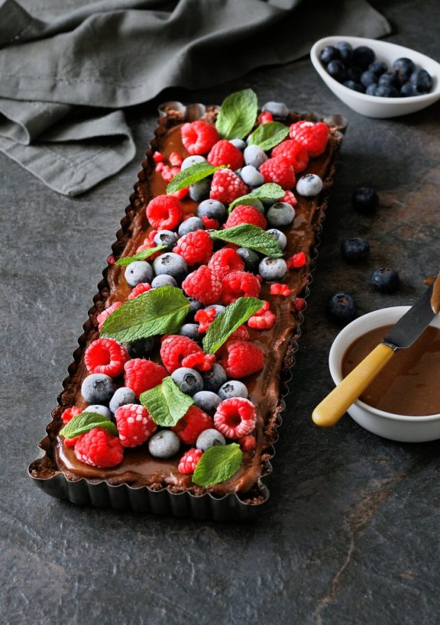 A dark moody photo of a vegan chocolate caramel tart that has been garnished with berries.