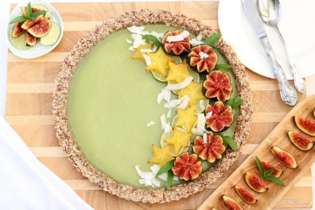 An overhead photo of a vegan coconut and lime tart that has been garnished with figs, lime slices and shredded coconut.