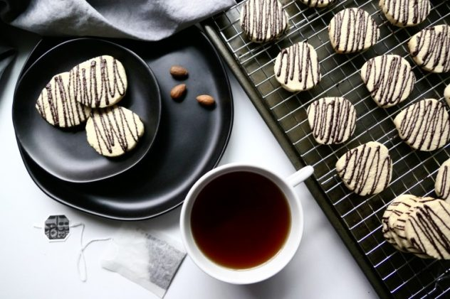 An overhead photo of vegan shortbread biscuits drizzled with chocolate with a cup of tea on the side.