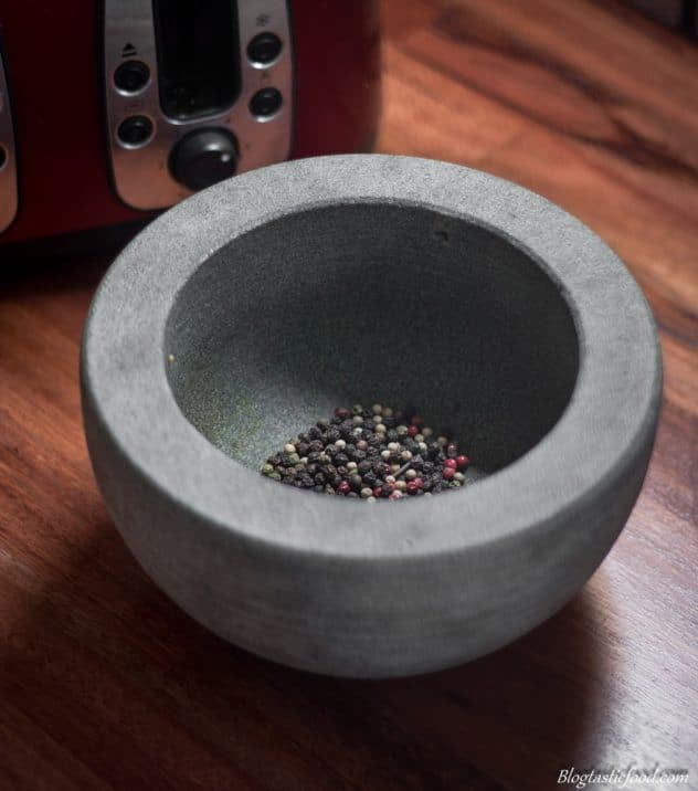 A handful of black peppercorns in a pestle mortar.