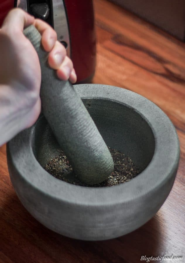 Someone crushing some black peppercorns in a pestle mortar.