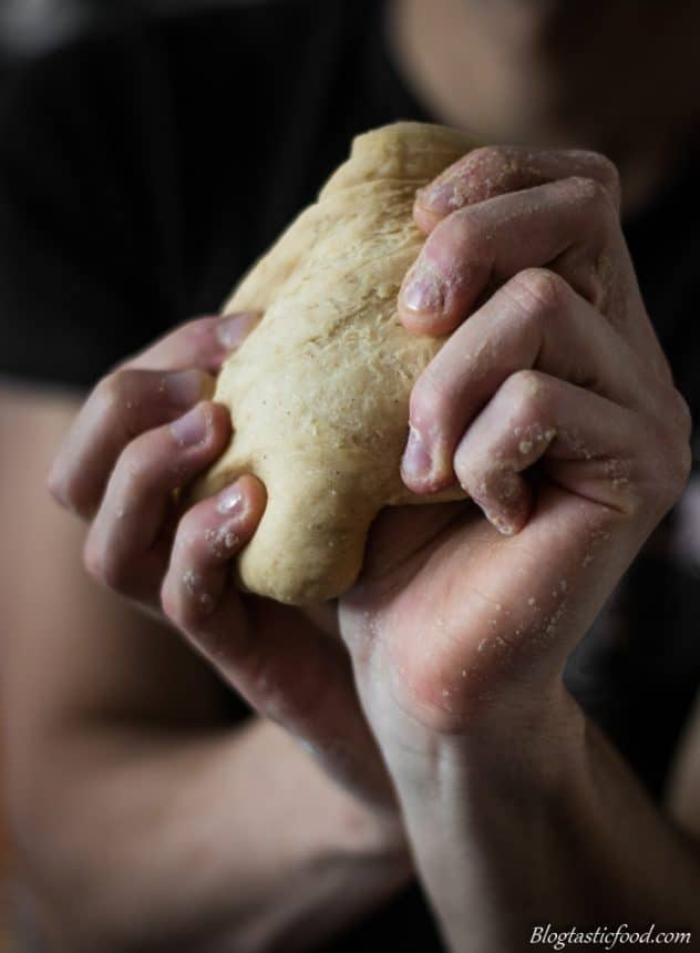 A photo of someone using their hands to stretch pasta dough.