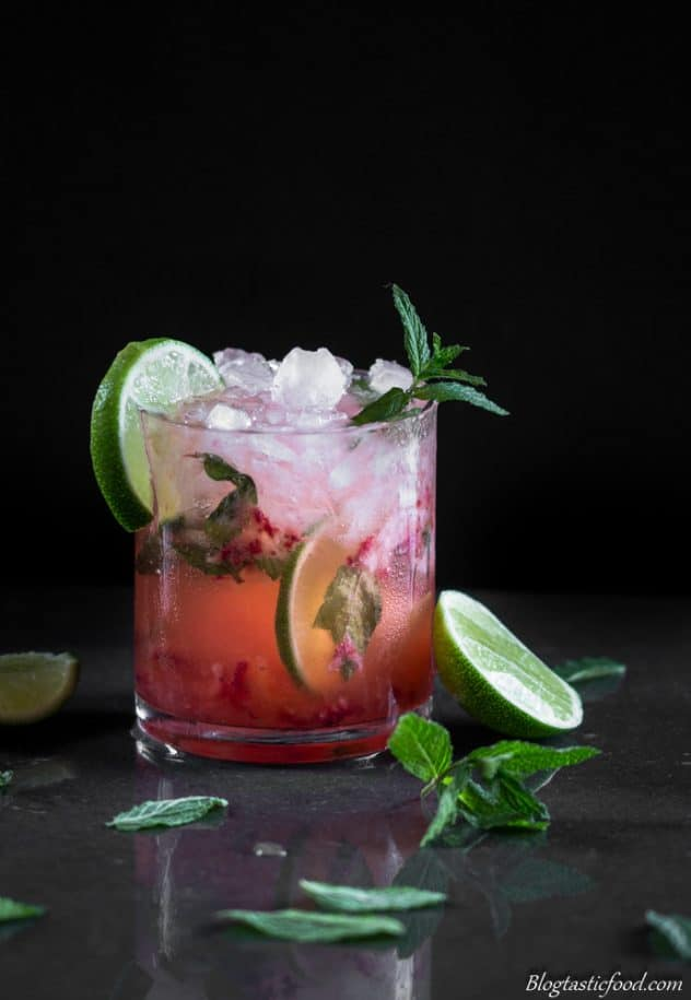 A photo of a strawberry mojito surrounded mint leaves.