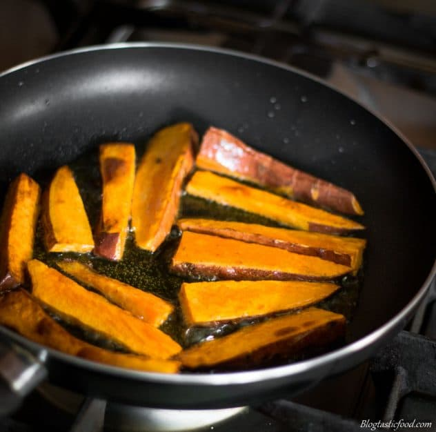 A photo of sweet potato wedges being pan fried in a non-stick pan.