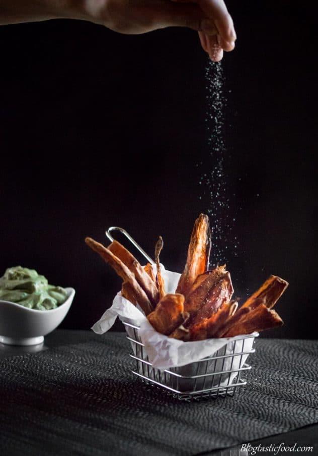 Salt being sprinkled over a basket of sweet potato wedges.