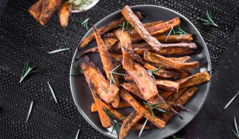 A photo of sweet potato wedges on a plate that has been garnished with rosemary.
