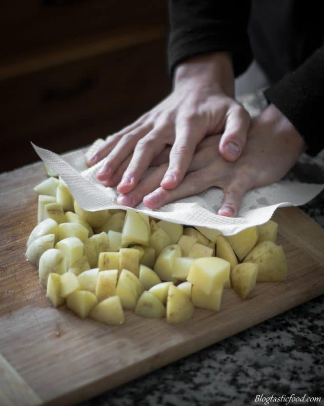 A photo of some using kitchen paper to soak up the moisture of diced potatoes.