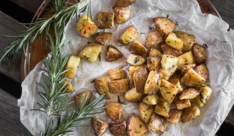 An overhead photo of roasted potatoes on a roasting tray lined with baking paper.