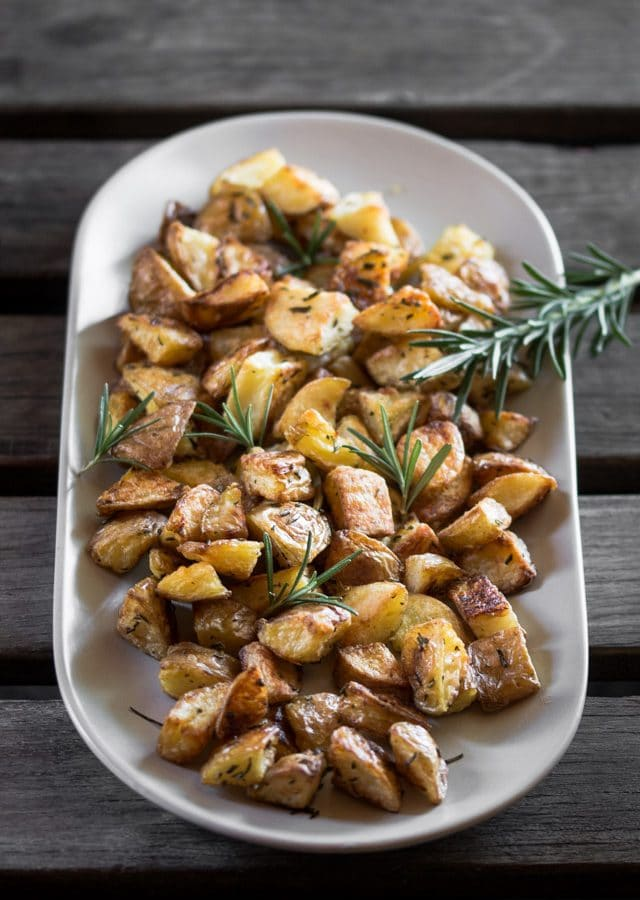 A picture of roasted potatoes and rosemary sprig served on a grey plate.