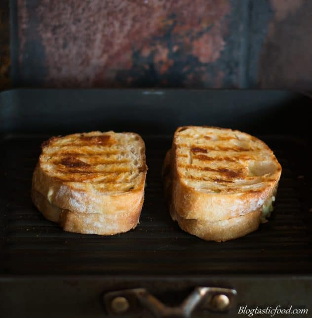 2 cheese sandwiches being grilled in a griddle pan.